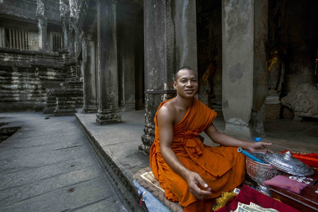 A Buddhist monk offering prayers, inside Angkor Wat Temple.